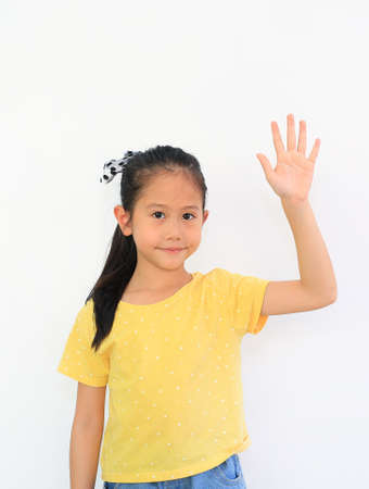 Asian little child girl holding hand up isolated on white background. Question and answer concept Stock Photo