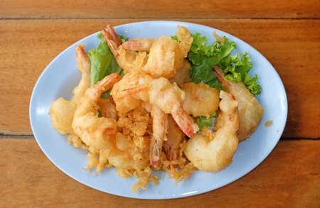 Deep fried peeled shrimp with flour in plate on wood table. Crispy seafood.