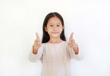 Portrait Asian little kid girl child pointing at you and looking camera isolated on blue background. Child point two index fingers to front