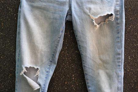 Torn blue Jeans on black gravel background. Denim texture with detail Reklamní fotografie