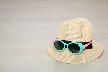 Summer hat with sunglasses on wooden laminate flooring background
