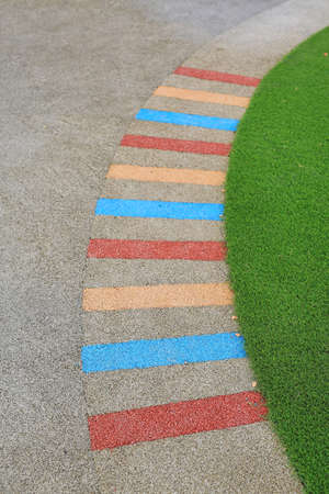 Cement path walkway and colorful stripes with green grass beside in the garden