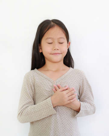 Portrait of Asian little girl closed eyes and holding hands on heart gesture of love. Kid place arms on chest isolated on white background. 免版税图像