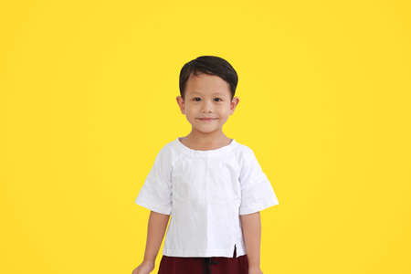 Portrait of happy smiling face asian little baby boy isolated on yellow background 免版税图像