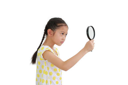 Asian little child girl looking through a magnifying glass to beside isolated on white background