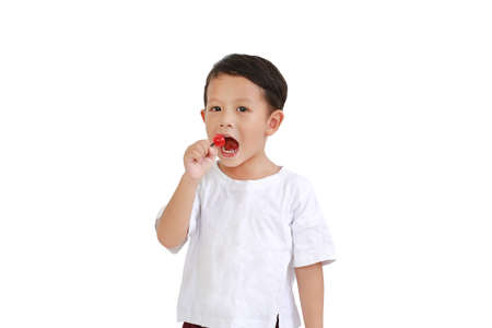 Portrait of asian little boy eating lollipop candy on white background
