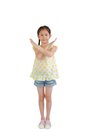 Asian little girl child crossed his hands gesture isolated on white background. Happy kid show stop sign or making X sign her arms and looking camera. Full length