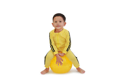 Asian little baby boy playing ride and sitting on round silicone inflatable yellow knobby ball isolated on white background