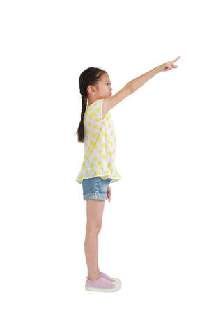 Asian little girl child pointing finger up beside isolated on white background - Full length 免版税图像