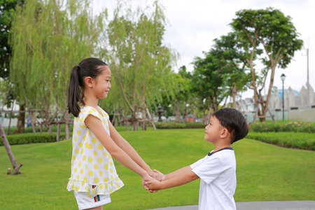 Smiling Asian little boy and girl child with hand in hand while playing together in the garden.
