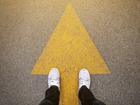 Feet and arrows on road Foto de archivo