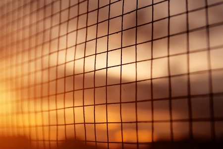 Silhouette of the iron fence with sunset background.