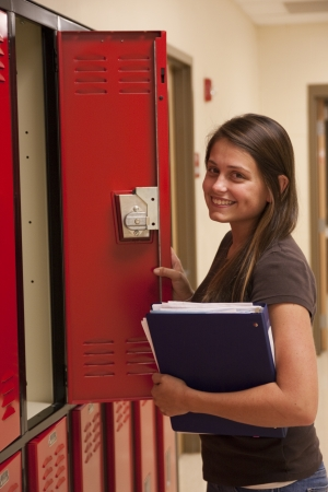 A female student smiles while opening her locker  Stock fotó