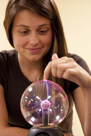 investigates: A female student investigates the properties of a plasma ball  Stock Photo