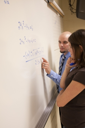 Bald teacher helping female student with a math problem on a whiteboard  photo