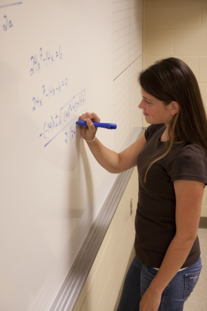 Female student solving an Algebra equation on a whiteboard  photo