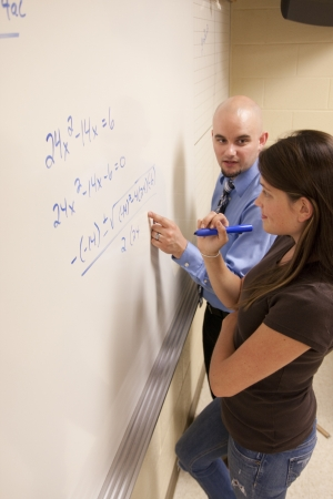Bald teacher helping female student with a math problem on a whiteboard