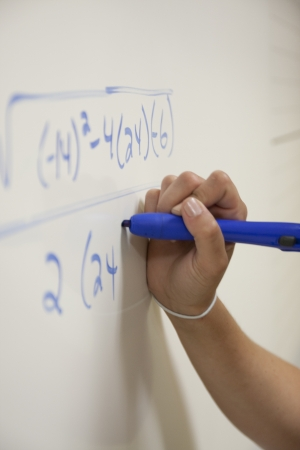 teenage girl: Hand solving an equation on a whiteboard with a blue marker