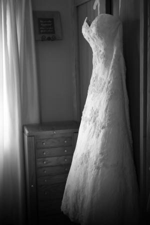 hangs: A bridal dress hangs from a closet