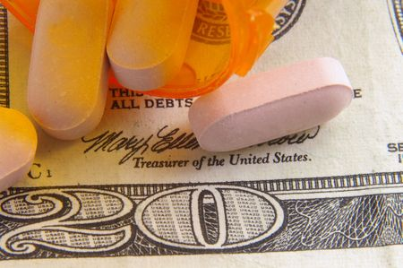 ingest: pink pills closeup on twenty-dollar bill