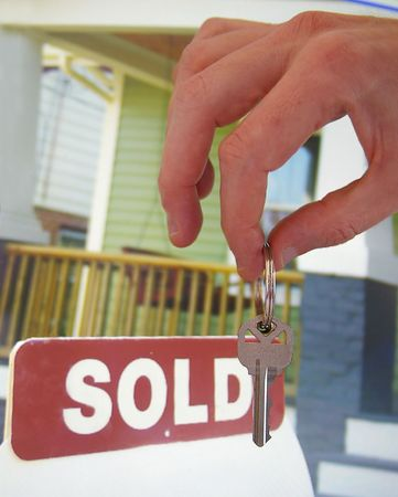 House for sale with sold sign and hand holding a key photo