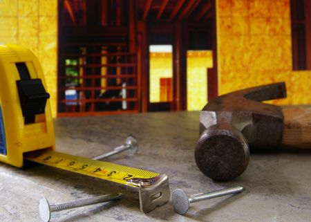 forceful: Hammer, nails, and tape measure with new home construction in background