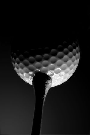 Golf ball on a tee shot from below in black and white
