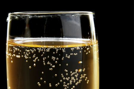 Champagne glass with bubbles on dark background. Could also be used as beer. Standard-Bild