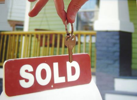 homeowner: Hand holding a house key in front of a  sold sign Stock Photo