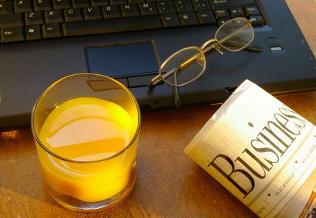 Cup of morning orange juice with laptop and newspaper Stock Photo - 717434