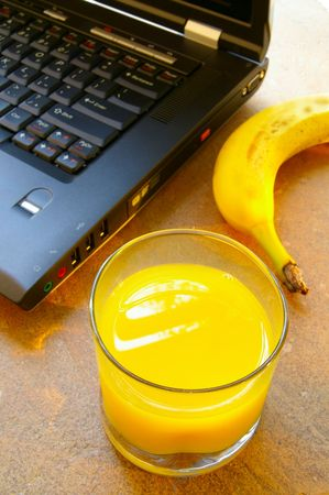 Cup of orange juice with laptop and banana Stock Photo