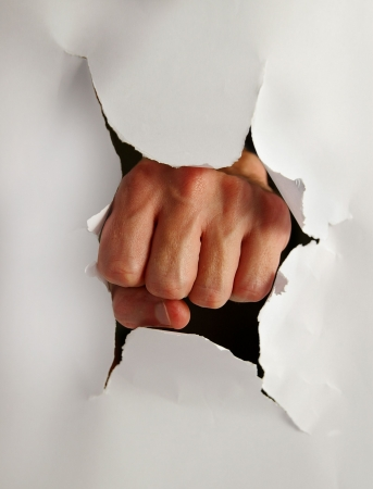 forceful: Fist punching thru paper creating a torn hole Stock Photo