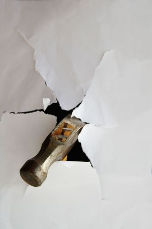 Hammer punching thru paper creating a torn hole Stock Photo - 849393