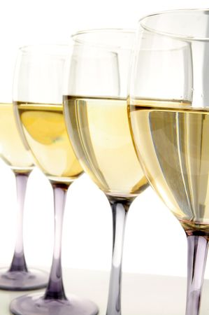 Glasses of white wine in a row on white