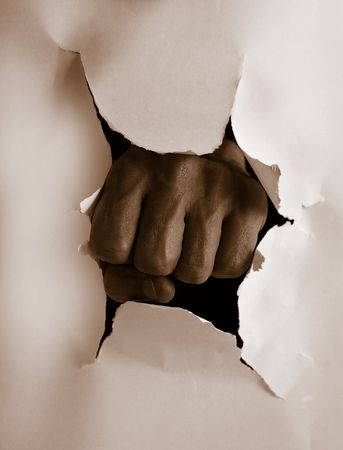 Fist punching thru paper creating a torn hole Stock Photo - 2111148