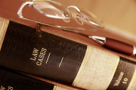 Closeup of law books with glasses and pen