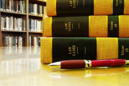 Lawbooks and a pen on a table,  in a library