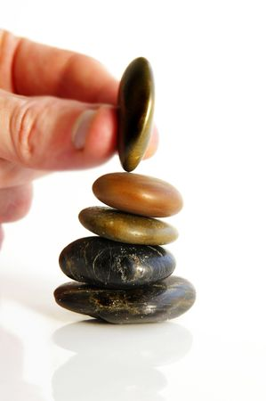 skillful: Hand placing a small stone on a stack of three