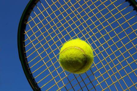 tennis racket: Tennis racket hitting ball against blue sky