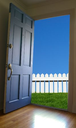 Door opening to green grass and blue sky photo