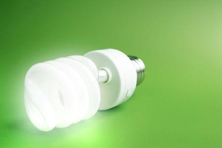 Compact fluorescent light bulb on green (green energy) Stock Photo