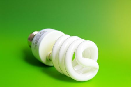 environmentalism: Compact fluorescent light bulb, closeup on green Stock Photo