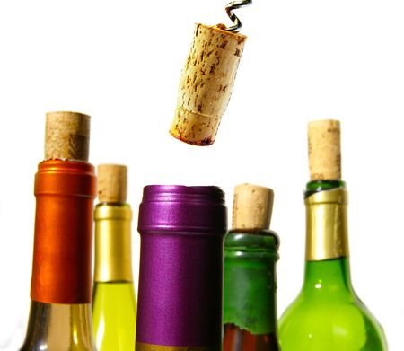 Colorful wine bottles and corks closeup on white photo