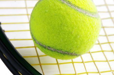 Closeup of a tennis ball and racket