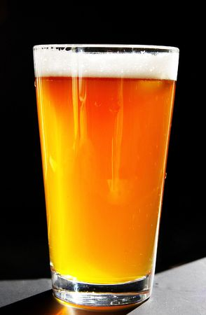 Full pint of amber beer with head, on dark background