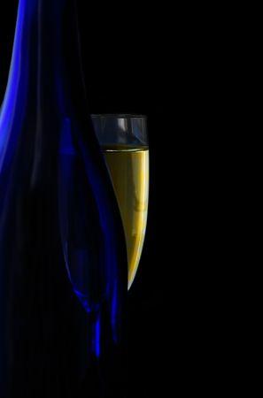 glazen fles champagne en blauw, op zwart Stockfoto