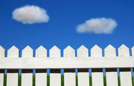 White picket fence, green grass and sky photo