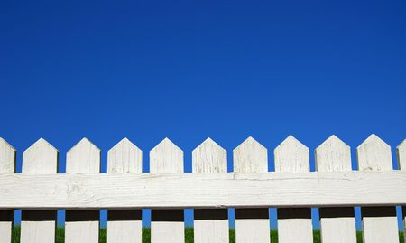 white picket fence: White picket fence, green grass and sky Stock Photo
