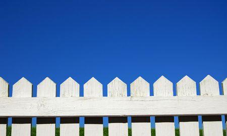 White piket omheining, groen gras en lucht