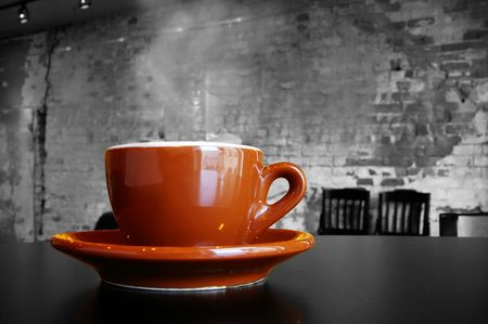 Cappuccino coffee cup and saucer in a brick cafe interior